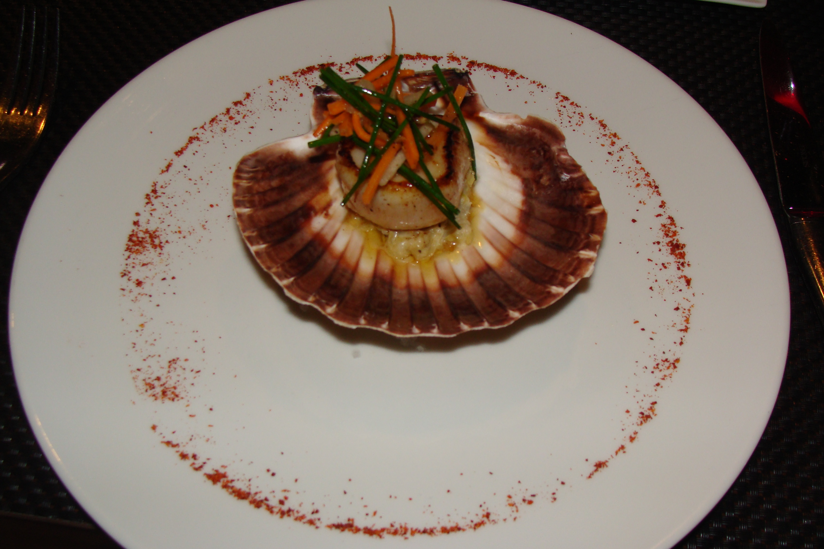 Scallops served on their own shell at London's L'Atelier by Joel Robuchon